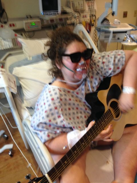 Tt playing the guitar she received for Christmas during her last hospital stay.